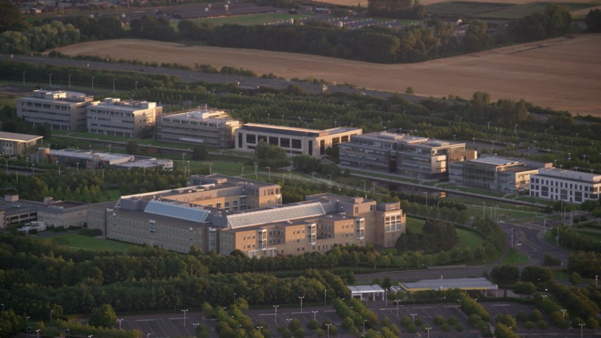 6K aerial stock footage video of passing by an office building at sunset in Edinburgh, Scotland Aerial Stock Footage | AX112_114