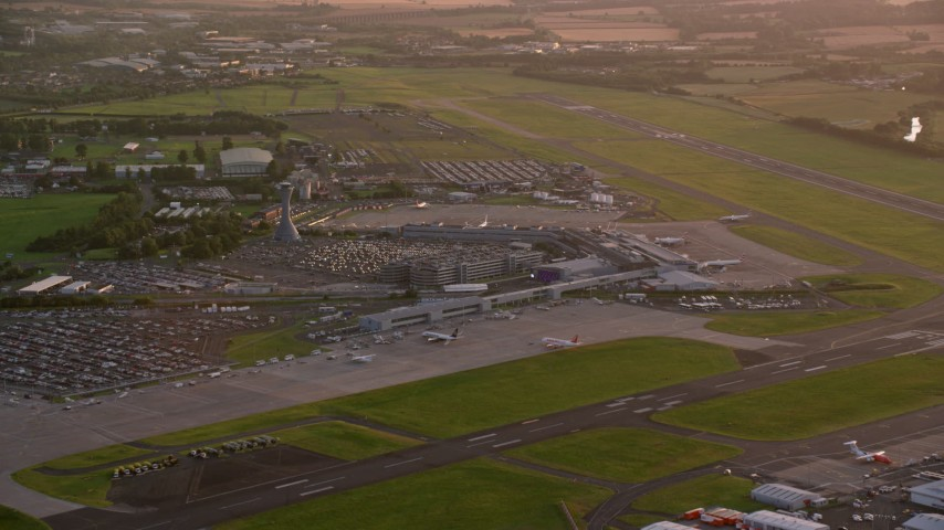 6K stock footage aerial video of flying by Edinburgh Airport, Scotland at sunset Aerial Stock Footage | AX112_116