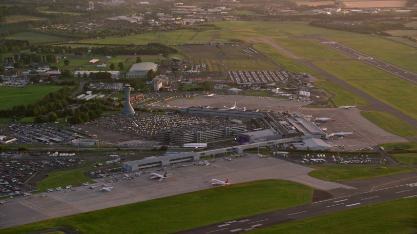 6K aerial stock footage video of passing by Edinburgh Airport at sunset, Scotland Aerial Stock Footage | AX112_117
