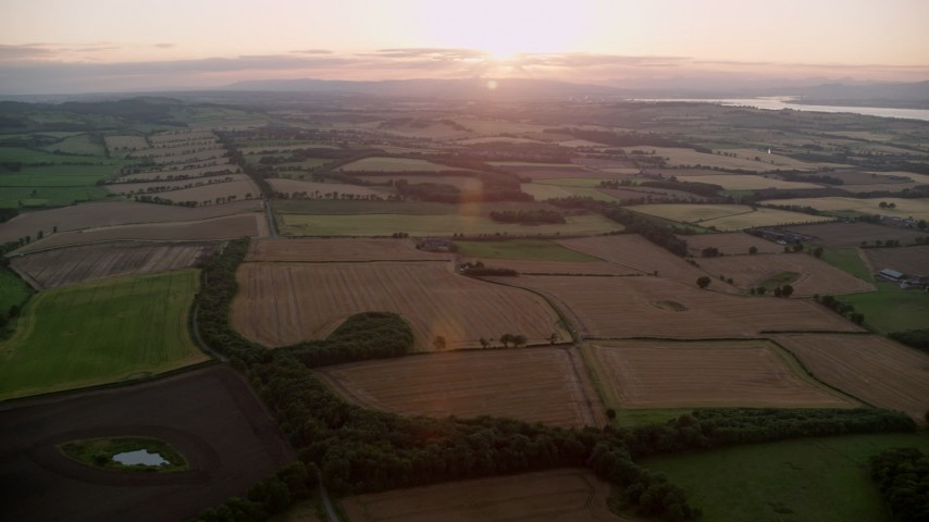 6K stock footage aerial video of farm fields with the sun setting, Broxburn, Scotland Aerial Stock Footage | AX112_129