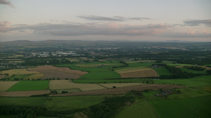 6K stock footage aerial video of flying by farming fields at sunset in Broxburn, Scotland Aerial Stock Footage | AX112_131