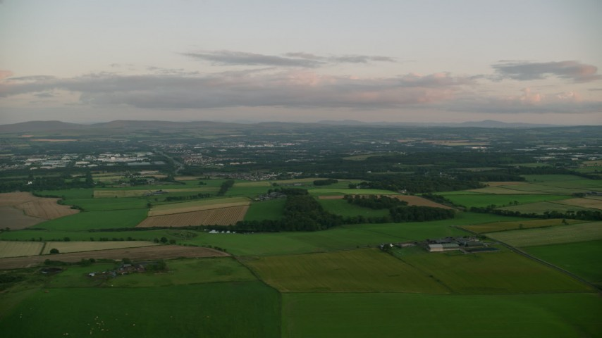 6K stock footage aerial video of passing by farm fields at sunset in Broxburn, Scotland Aerial Stock Footage | AX112_132