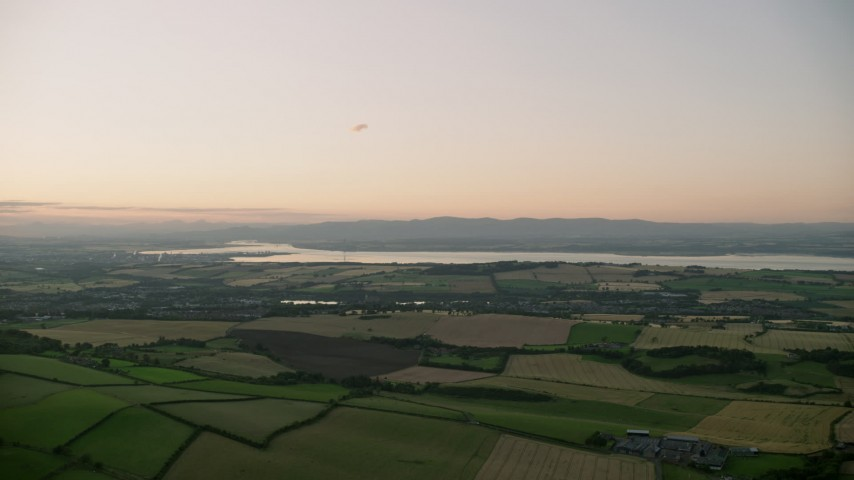 6K aerial video pan across farming fields at sunset in Linlithgow, Scotland Aerial Stock Footage | AX112_134