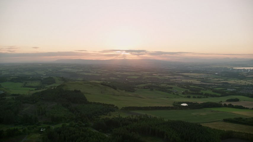 6K aerial video of sun setting over farmland, Linlithgow, Scotland Aerial Stock Footage | AX112_136