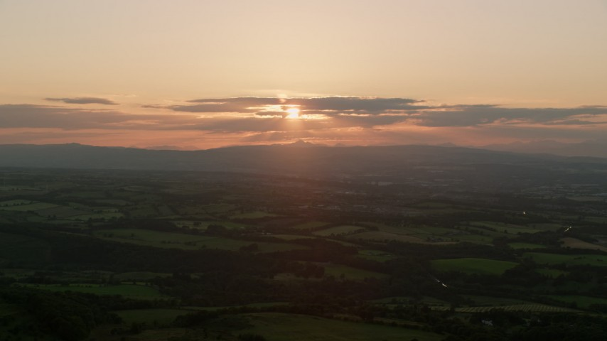 6K aerial video of the setting sun over farmland in Linlithgow, Scotland Aerial Stock Footage | AX112_137