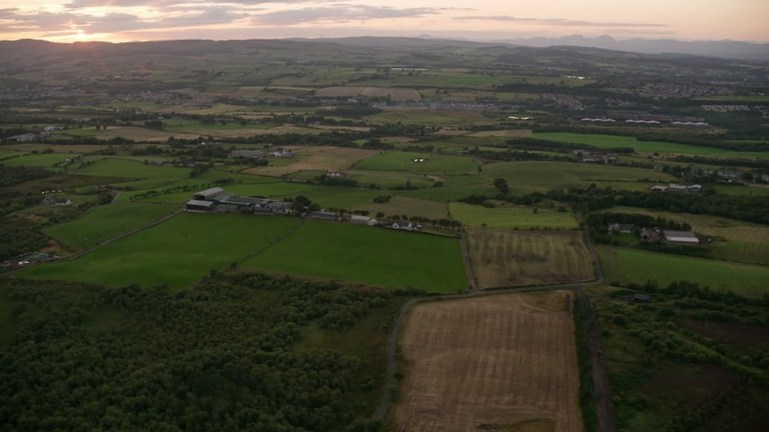 6K stock footage aerial video of passing farms and fields in Bonnybridge, Scotland at twilight Aerial Stock Footage AX112_155 | Axiom Images