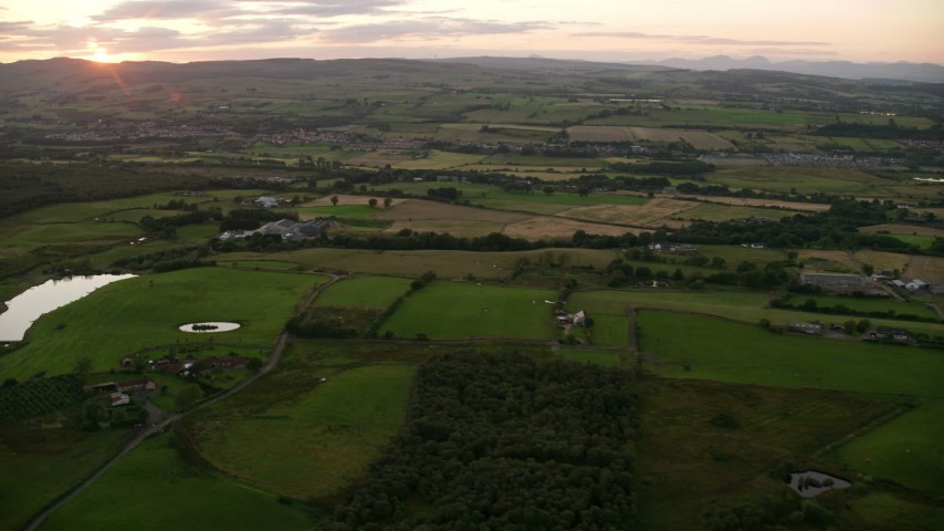 6K stock footage aerial video of passing by farms and farm fields at sunset in Bonnybridge, Scotland Aerial Stock Footage | AX112_156
