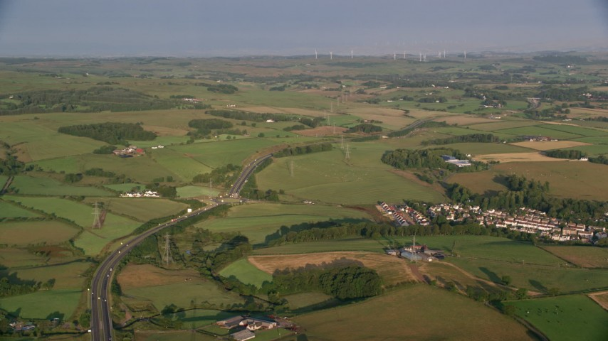 6K stock footage aerial video of farms, fields and rural homes near A726 Highway, Glasgow, Scotland at sunrise Aerial Stock Footage | AX113_005