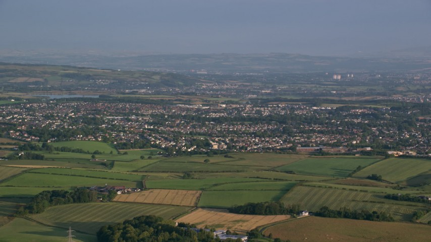 6K stock footage aerial video of farming fields near rural residential neighborhoods in Glasgow, Scotland at sunrise Aerial Stock Footage | AX113_008
