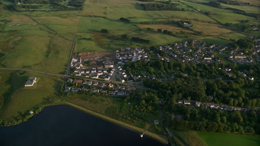 6K stock footage aerial video of orbiting homes in the village of Eaglesham, Scotland at sunrise Aerial Stock Footage | AX113_009