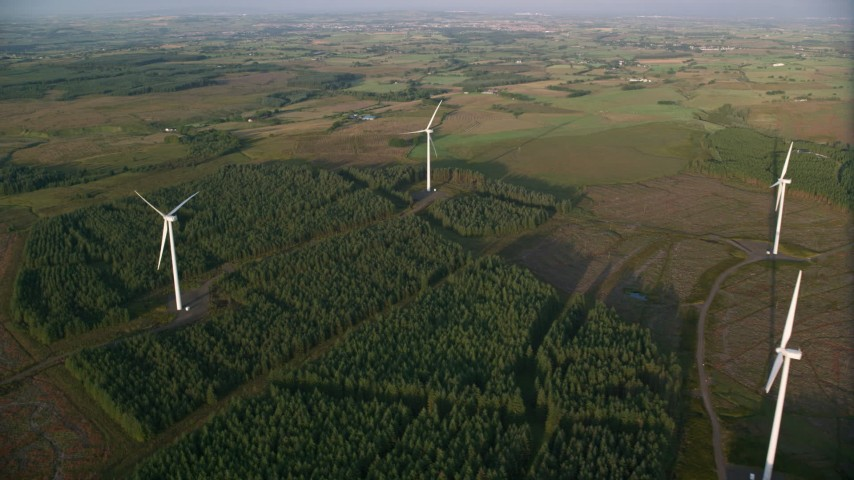 6K stock footage aerial video fly over windmills and trees, Eaglesham, Scotland at sunrise Aerial Stock Footage | AX113_020