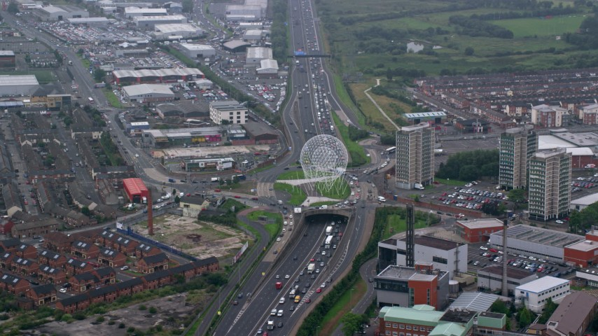 6K aerial video of the Rise sculpture and M1 Freeway near office buildings, Belfast, Northern Ireland Aerial Stock Footage | AX113_093