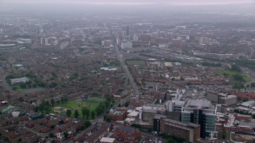6K stock footage aerial video of following street past hospital near neighborhood, Belfast, Northern Ireland Aerial Stock Footage | AX113_099
