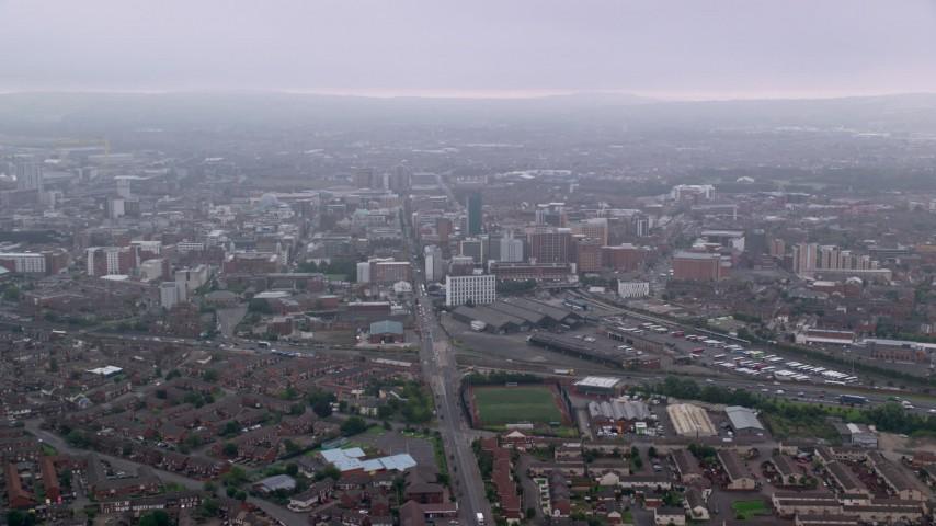 6K stock footage aerial video follow Grosvenor Road toward office buildings, Belfast, Northern Ireland Aerial Stock Footage | AX113_100
