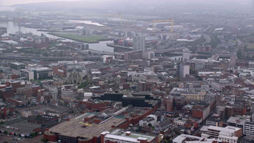 6K stock footage aerial video fly over city buildings toward the river, Belfast, Northern Ireland Aerial Stock Footage | AX113_115