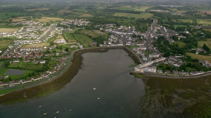 6K stock footage aerial video orbiting a waterfront village and fields, Strangford Lough, Killyleagh, Northern Ireland Aerial Stock Footage | AX113_153