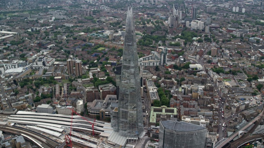 6K stock footage aerial video of The Shard skyscraper towering over city buildings, London, England Aerial Stock Footage | AX114_077