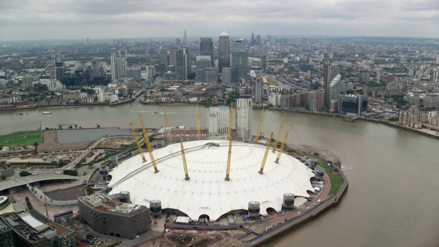 6K stock footage aerial video approach The O2 arena and Canary Wharf skyscrapers by the River Thames, London, England Aerial Stock Footage | AX114_146