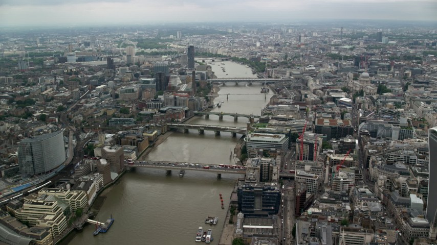 6K stock footage aerial video of flying over London Bridge toward other bridges over the River Thames, England Aerial Stock Footage AX114_161