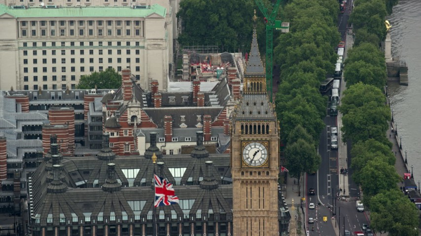 6K stock footage aerial video of famous Big Ben and the British Flag, London, England Aerial Stock Footage | AX114_221