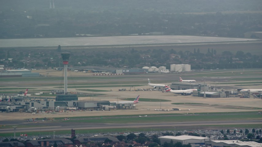 6K stock footage aerial video of the control tower and airliner at London Heathrow Airport, England Aerial Stock Footage | AX114_287