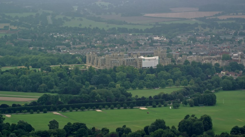 6K stock footage aerial video of Windsor Castle surrounded by green trees, England Aerial Stock Footage | AX114_302