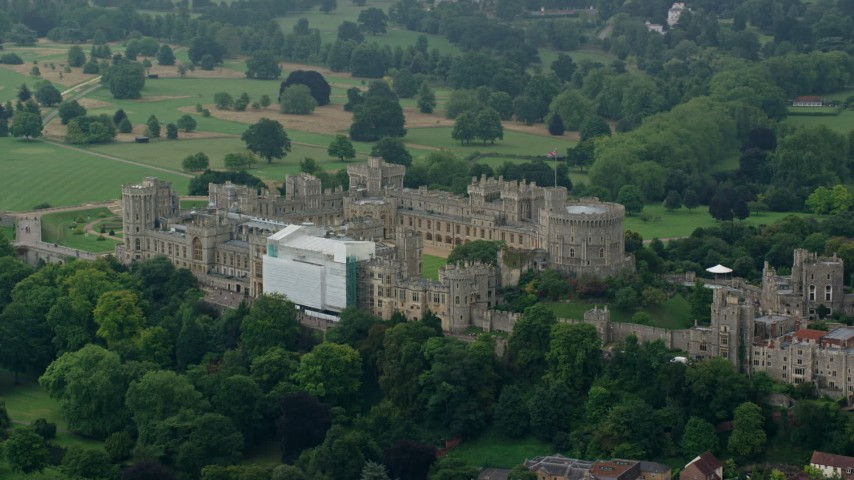 6K stock footage aerial video of circling around the side of Windsor Castle among trees, England Aerial Stock Footage | AX114_318