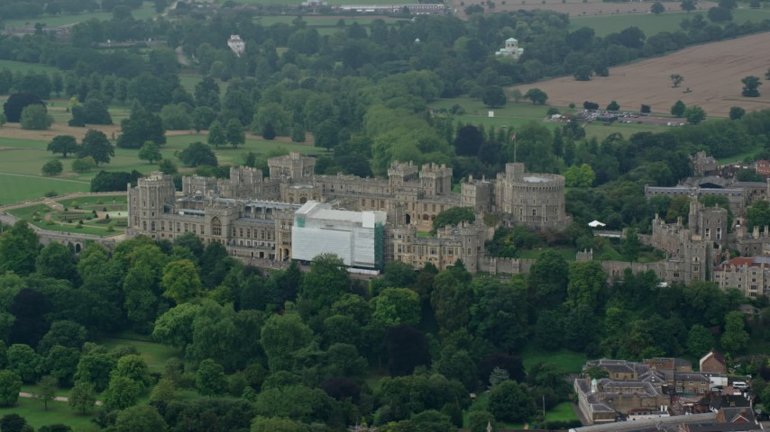 6K stock footage aerial video of a reverse view of Windsor Castle among trees, England Aerial Stock Footage | AX114_319