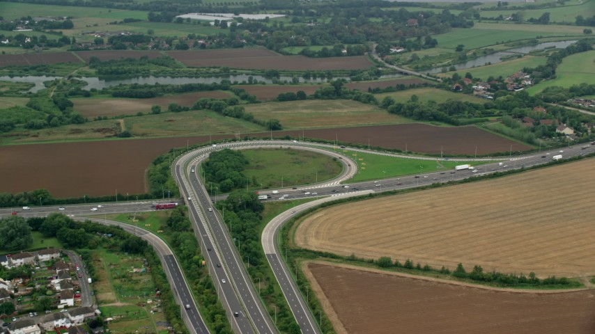 6K stock footage aerial video of orbiting M4 Freeway Interchange by farmland, Windsor England Aerial Stock Footage | AX114_324