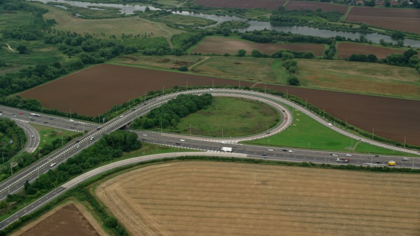 6K stock footage aerial video of an orbit of M4 Freeway Interchange by farmland, Windsor, England Aerial Stock Footage | AX114_325