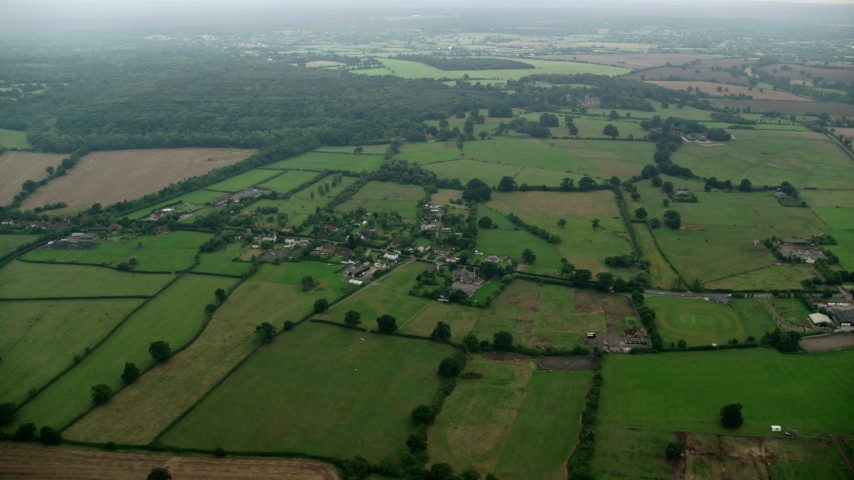 6K stock footage aerial video of flying over rural homes and farmland, Windsor, England Aerial Stock Footage | AX114_331