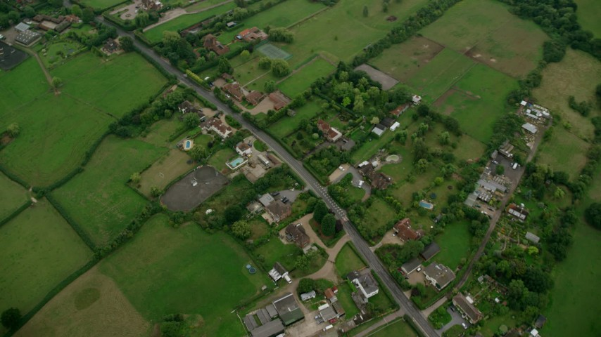 6K stock footage aerial video tilt to bird's eye view of farm fields and rural homes, Windsor, England Aerial Stock Footage | AX114_332