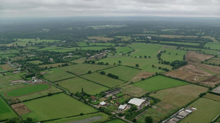 6K stock footage aerial video of flying over a rural landscape with farm fields in Windsor, England Aerial Stock Footage | AX114_335