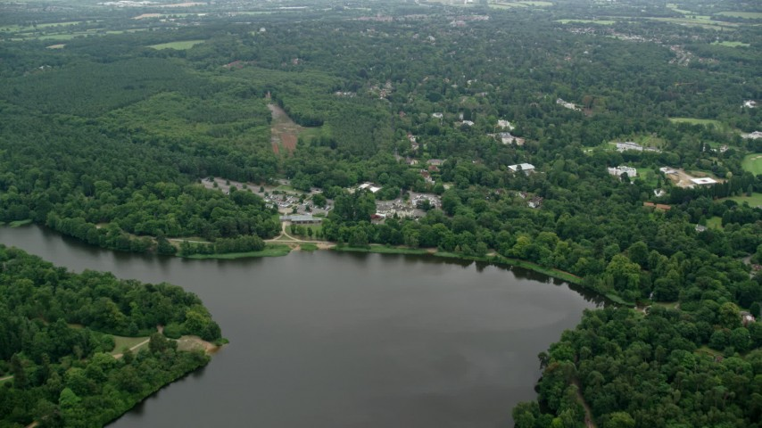 6K stock footage aerial video of flying over Virginia Water Lake toward homes, England Aerial Stock Footage | AX114_346