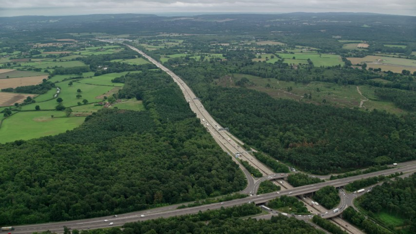 6K stock footage aerial video of M25 Freeway through farmland and forests, Cobham, England Aerial Stock Footage AX114_359 | Axiom Images