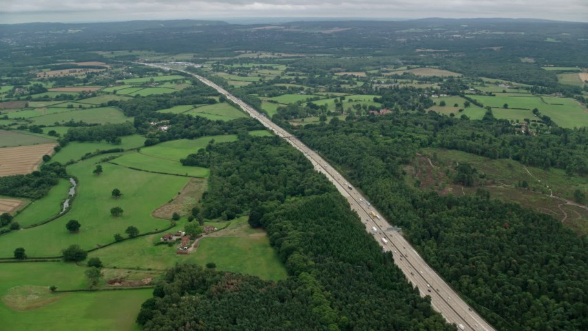 6K stock footage aerial video of following the M25 Freeway through farmland and forests, Cobham, England Aerial Stock Footage | AX114_360