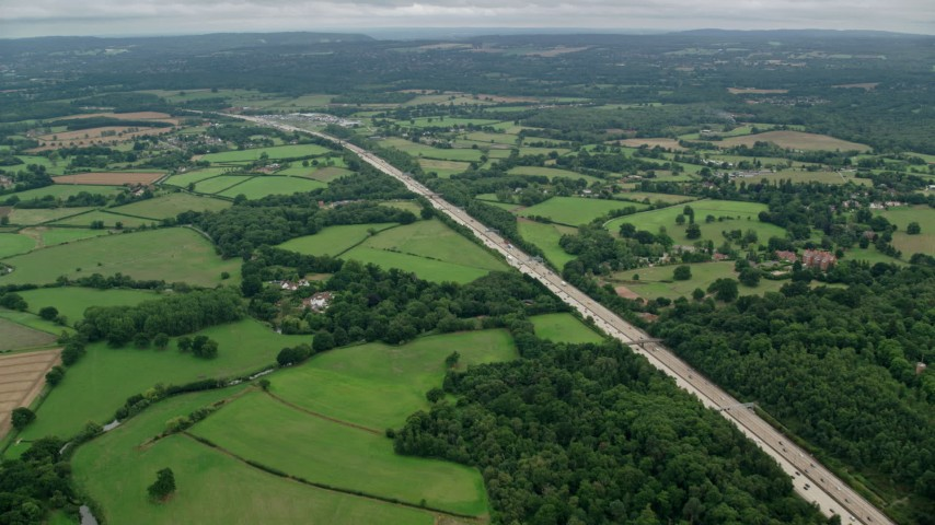 6K stock footage aerial video following the M25 Freeway past farmland and forests, Cobham, England Aerial Stock Footage | AX114_361