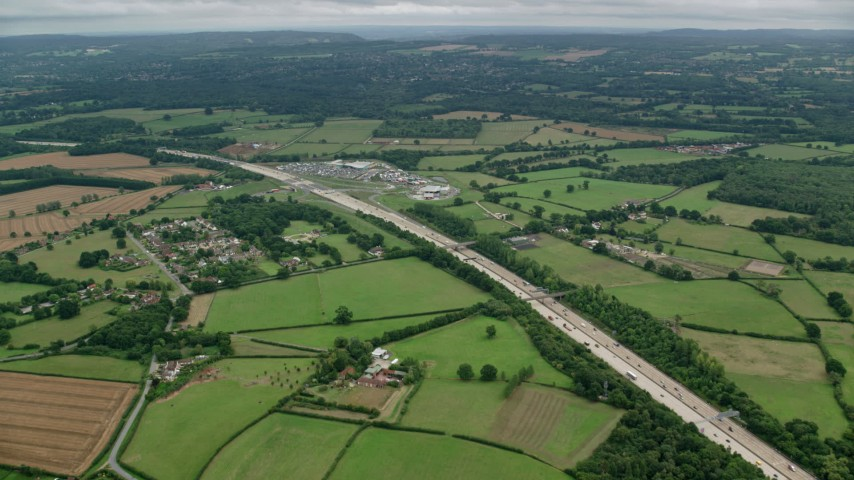 6K stock footage aerial video of the M25 through farmland past homes and shopping center, Cobham, England Aerial Stock Footage | AX114_363