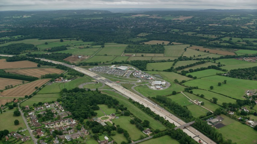 6K stock footage aerial video approach shopping center by farm fields, homes and freeway, Cobham, England Aerial Stock Footage | AX114_364