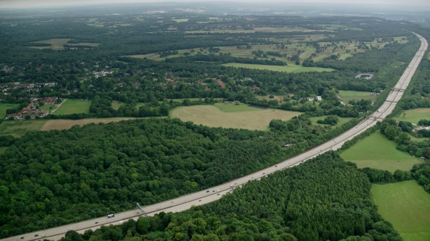 6K stock footage aerial video approach freeway, farm fields and trees, Tadworth, England Aerial Stock Footage | AX114_374