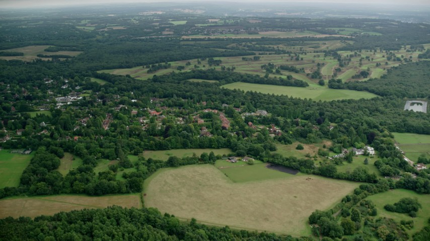 6K stock footage aerial video of village homes and trees near Walton Heath Golf Club in Tadworth, England Aerial Stock Footage AX114_375
