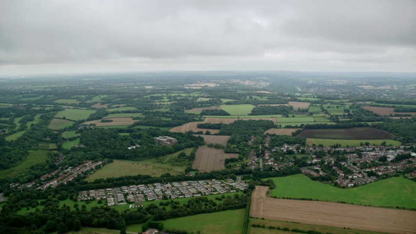 6K stock footage aerial video fly over rural homes and approach farm fields, Tadworth, England Aerial Stock Footage | AX114_377