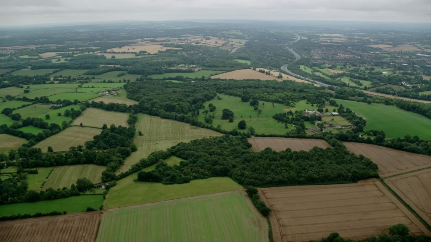 6K stock footage aerial video of flying over fields and trees, Tadworth, England Aerial Stock Footage | AX114_378