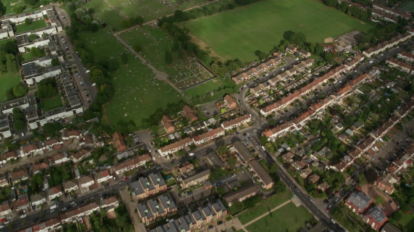 6K stock footage aerial video bird's eye view of residential neighborhoods, reveal a cemetery, London, England Aerial Stock Footage | AX115_047