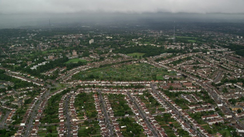 6K stock footage aerial video fly over suburban homes with rain in the distance, London, England Aerial Stock Footage | AX115_049