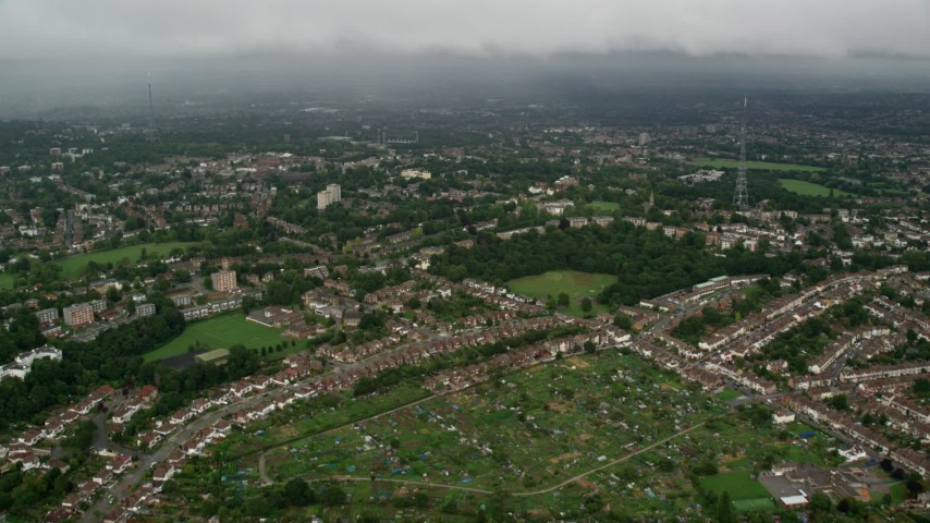 6K stock footage aerial video fly over residential neighborhoods approaching rain in the distance, London, England Aerial Stock Footage | AX115_050