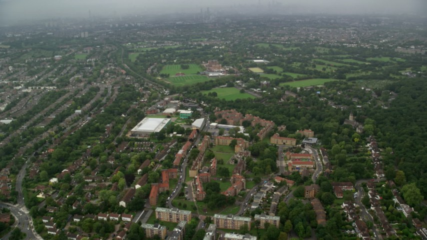 6K stock footage aerial video of approaching Kingsdale School in rain, London, England Aerial Stock Footage | AX115_053
