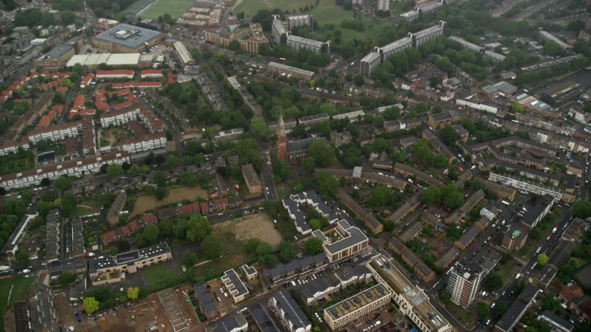 6K stock footage aerial video tilt to St John the Divine church by apartment buildings in the rain, London, England Aerial Stock Footage | AX115_057