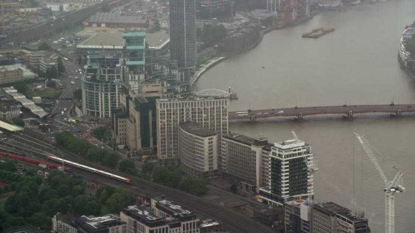 6K stock footage aerial video of MI6 Building and Vauxhall Bridge over the River Thames in the rain, London, England Aerial Stock Footage | AX115_061