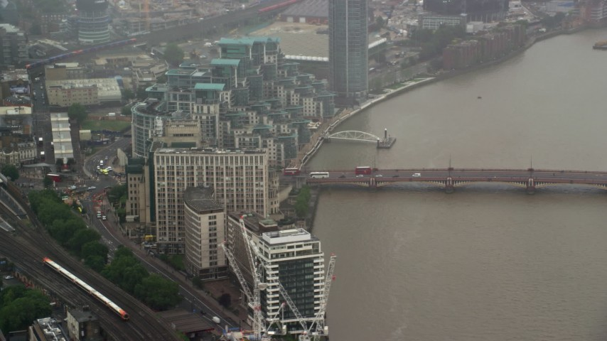 6K stock footage aerial video of orbiting MI6 Building and Vauxhall Bridge in the rain, London, England Aerial Stock Footage | AX115_062